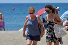 Dos mujeres con mascarillas caminan por la playa de El Zapillo en Almería