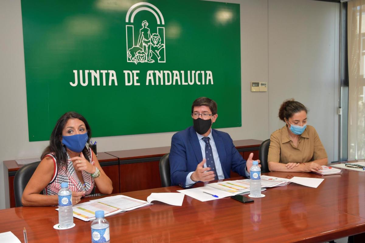 Juan Marín, entre la presidenta de Parlamento andaluz, Marta Bosquet (i), y la presidenta de la Cruz Roja en Andalucía, María del Mar Pageo (d).