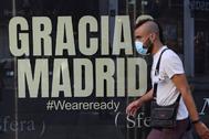 Un joven pasea por el centro de Madrid junto a un mensaje de agradecimiento a la ciudad.