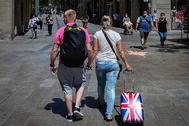 Una pareja de turista británicos pasean, este lunes, por las calles de Barcelona.