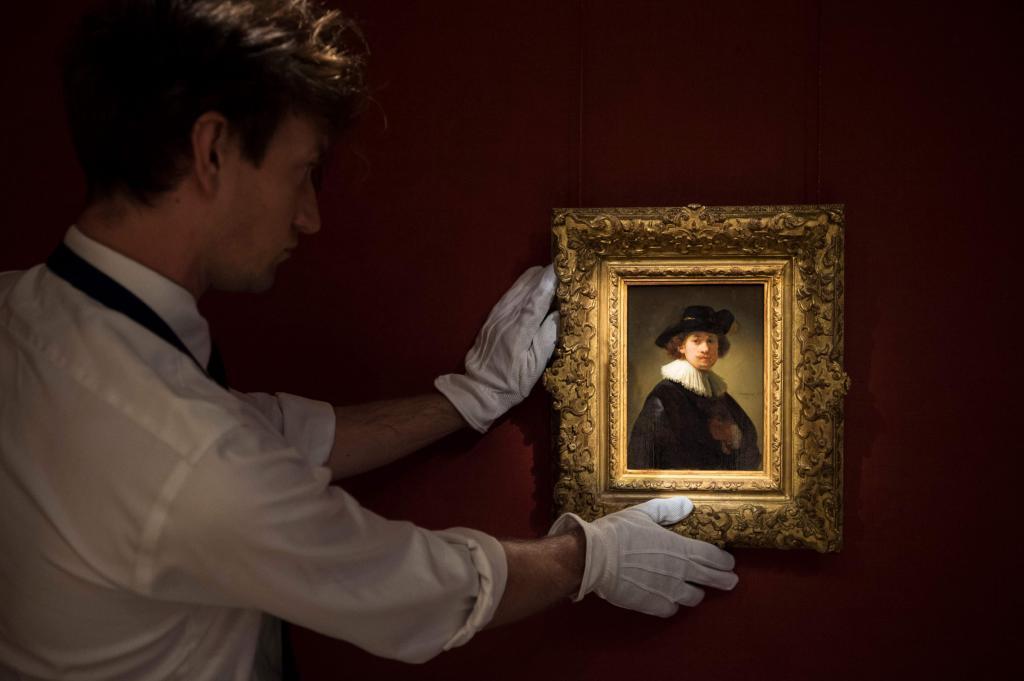 Un operario de Sotheby's con el autorretrato subastado de Rembrandt.