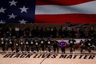 Jugadores de Lakers y Clippers, arrodillados durante el himno.
