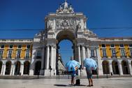 Guías turísticos esperan a los clientes, en la Plaza del Comercio de Lisboa.