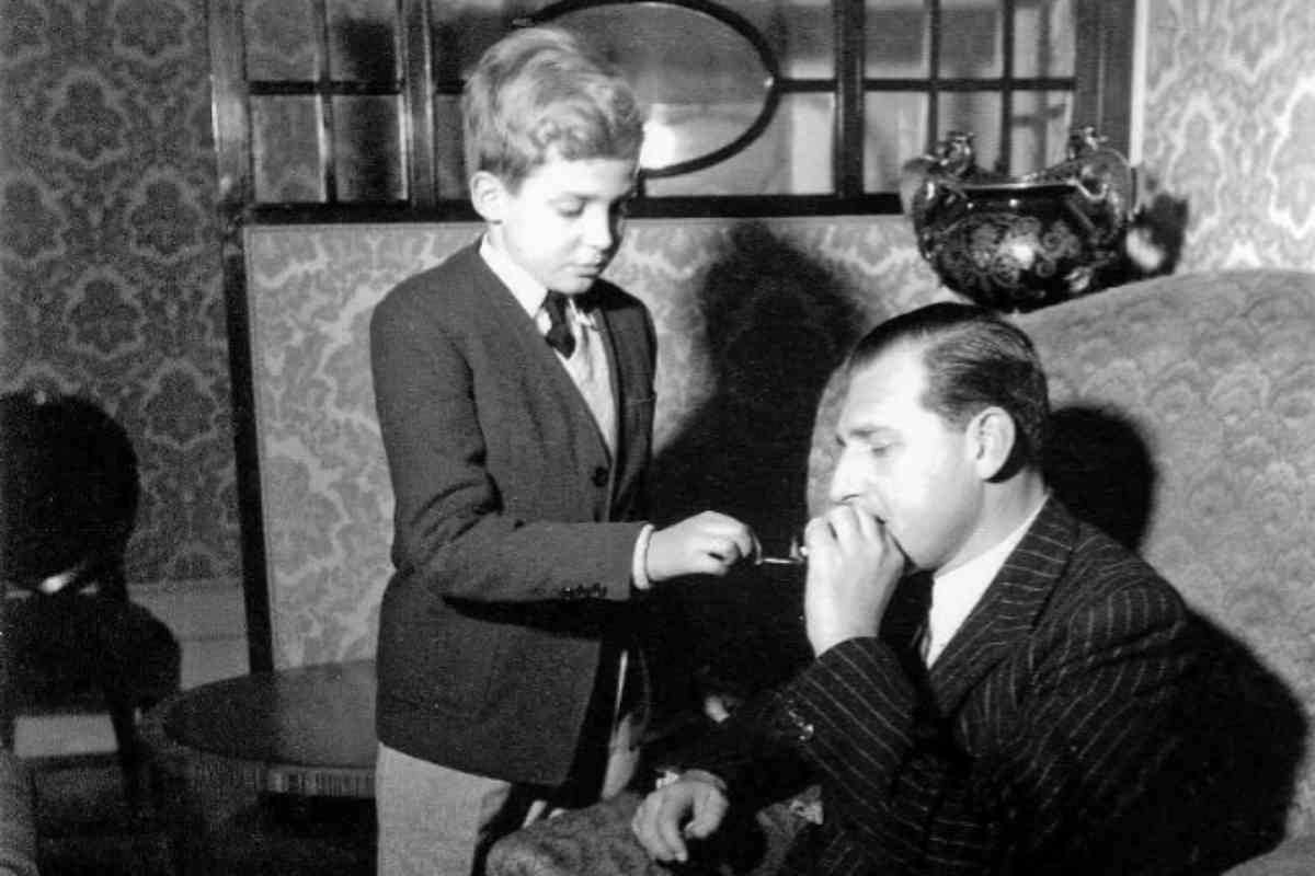 Don Juan Carlos, de niño junto a su padre, el Conde de Barcelona, en una foto en la que le enciende un cigarro, tomada a finales de los 40 en Estoril, cuando la familia real española vivía en el exilio en el palacio Villa Giralda.