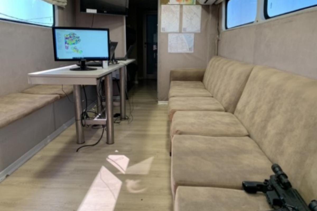 Interior de la autocaravana, con una ametralladora sobre el sofá.