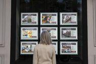 Una mujer consulta los carteles en el escaparate de una inmobiliaria de Madrid.