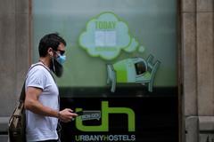 Un hombre pasea con mascarilla por Barcelona