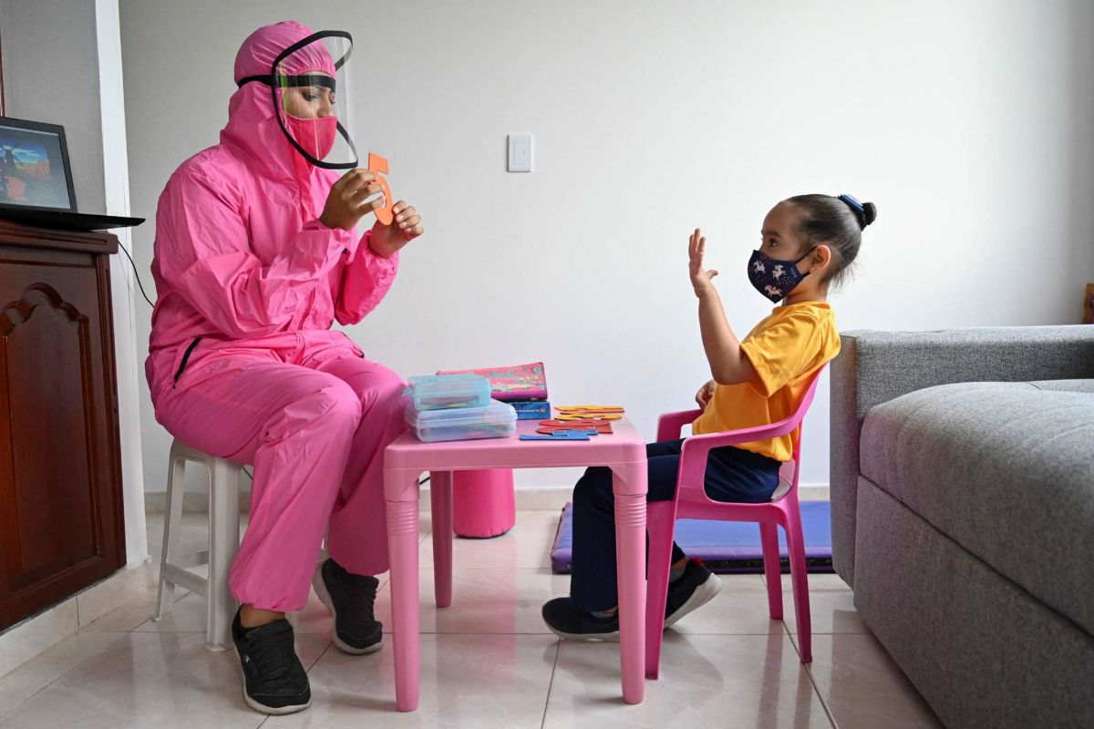 Una maestra enseña a una niña en Cali (Colombia).