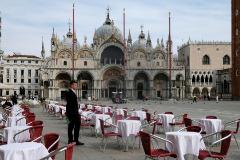 Un camarero espera, rodeado de mesas vacías, en la Plaza San Marcos.