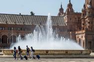 Un grupo de turistas atraviesa la Plaza de España de Sevilla bajo el sol de agosto.