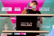 Una mujer limpia el atril durante la presentación del Festival de Cine de Málaga.