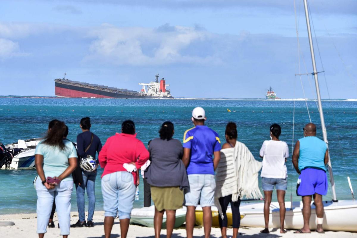 Varias personas observan el carguero desde la orilla.