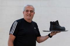 Julio Carballeda, con una de sus botas de trabajo, tras aplazar sus labores como camarero.