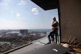 Un hombre, herido por las explosiones, se sienta en su casa destruida de Mar Mikhael (Beirut), con vistas al puerto.