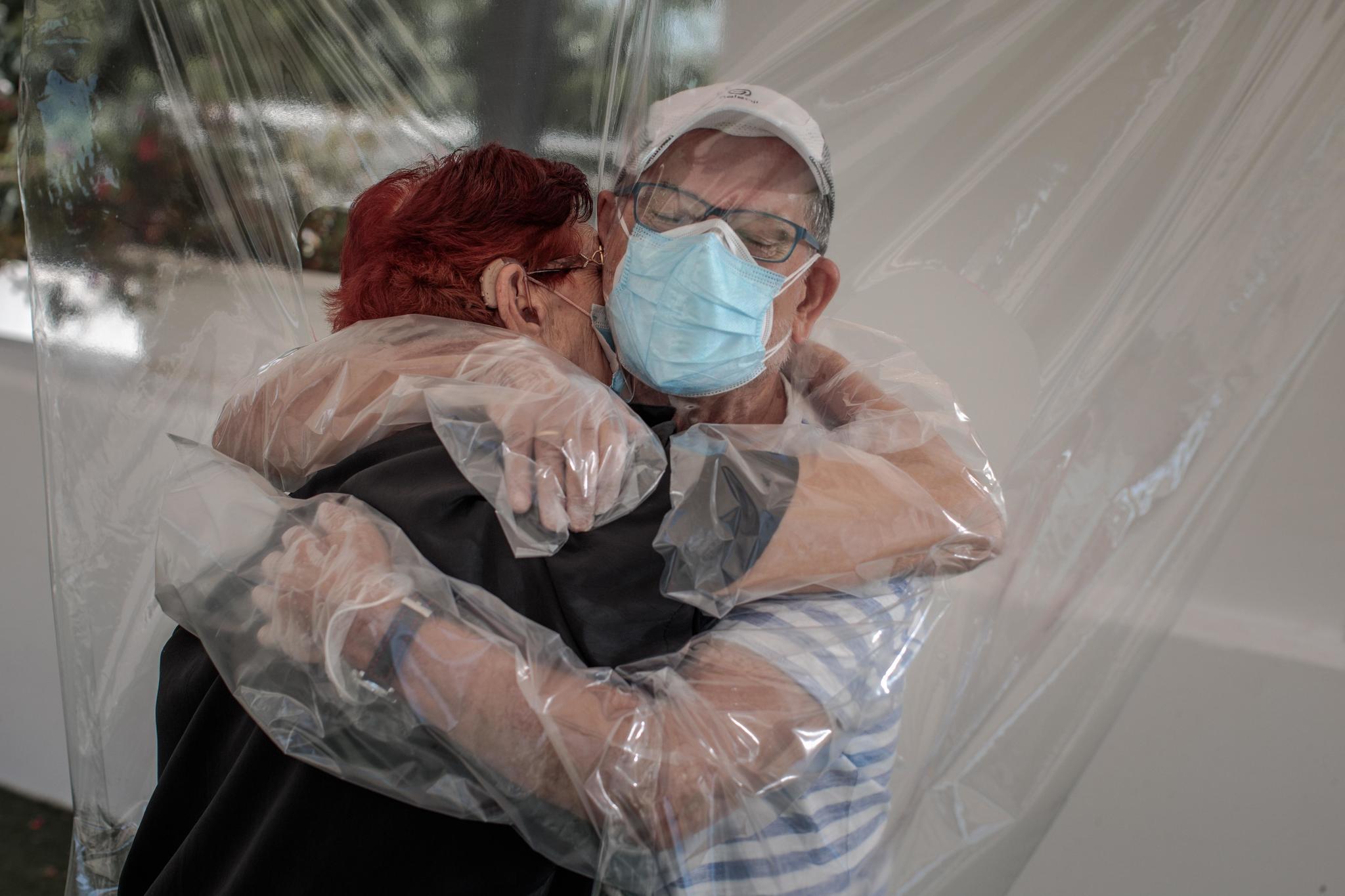 Una residente abraza a un familiar a través de un plástico en junio de 2020.