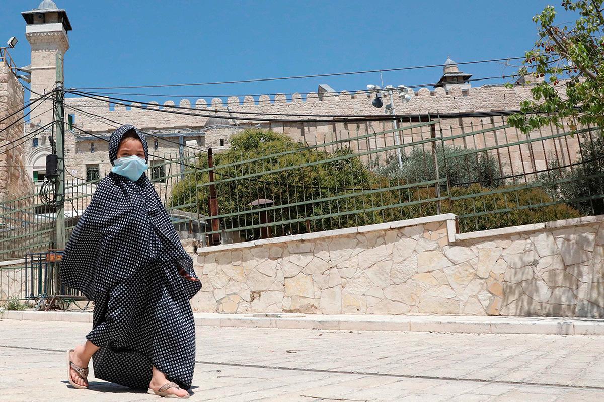 Una niña palestina camina junto a la mezquita Ibrahimi en la ciudad ocupada de Hebrón, en Cisjordania.