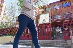 Un chico camina con un móvil frente a un colegio de Madrid.