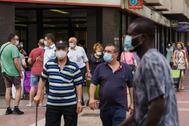 Vecinos con mascarilla en el barrio de Las Delicias de Zaragoza