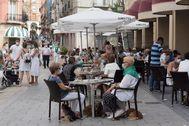 Varias personas, sentadas en una terraza, en Huesca.