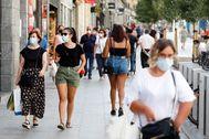 Varias personas, protegidas con mascarillas, circulan por la calle Carretas de Madrid