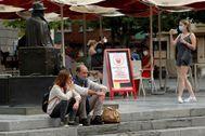 Una pareja de turistas fuman en una plaza de Oviedo