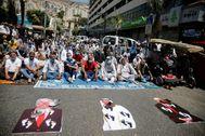 Palestinos protestan junto a imágenes de Donald Trump, Mohammed bin Zayed y Benjamin Netanyahu.