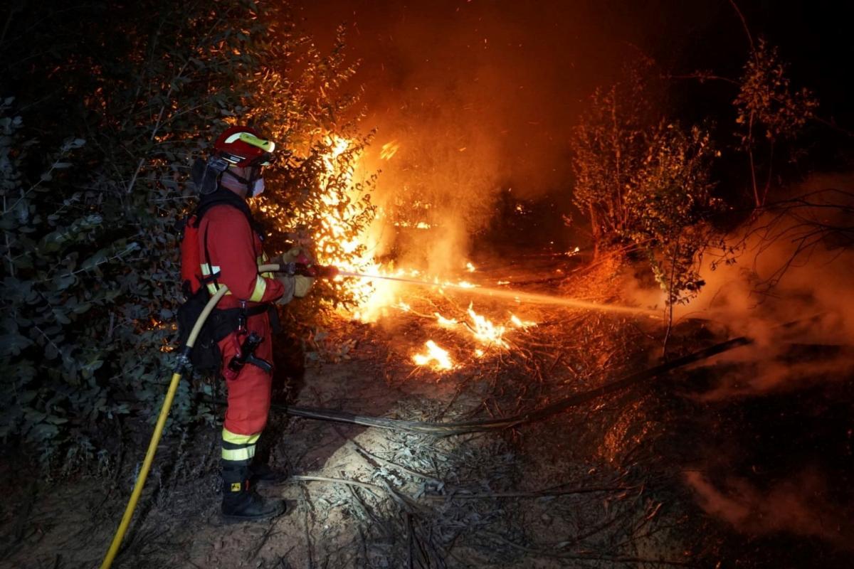 Bombero intenta extinguir las llamas en el incendio de Almonaster la Real.