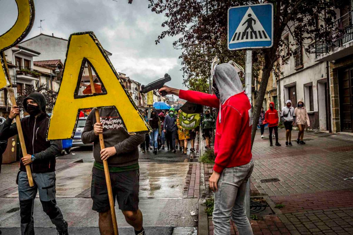 Un manifestante apunta con un arma a otro manifestante.