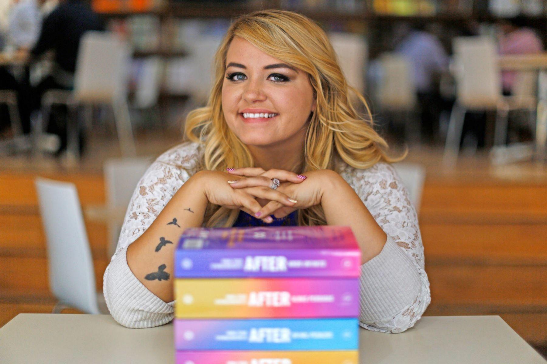 Anna Todd, la creadora de la saga, juntos  sus libros.