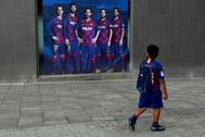Un niño mira un póster promocional del Barça con Messi.