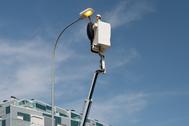 Un operario del proyecto de Telefónica, Ferrovial y Tellink cambia una farola pública.
