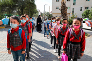 Profesores palestinos comprueban la temperatura de sus alumnos el primer día de clases, en Hebrón.