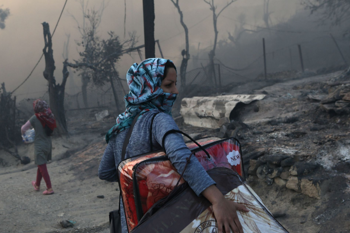 Una mujer abandona el campamento cargando sus pertenencias.