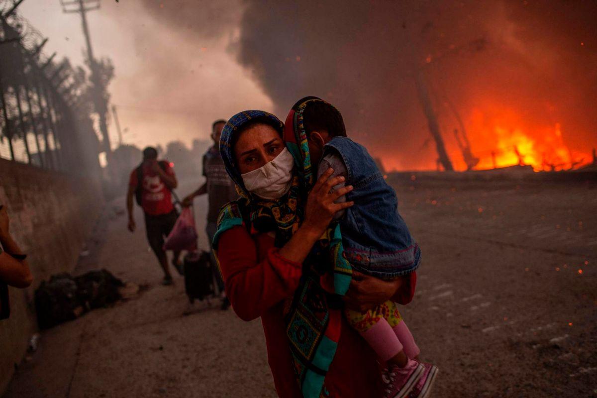 Una mujer con su hijo huye de las llamas en Moria.