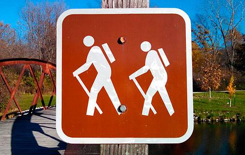 Señal de senda excursionista en la que la mujer sigue al hombre.