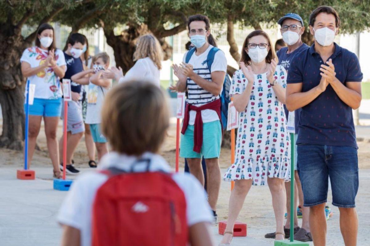 Los profesores del CEIPTomás Ybarra, en la localidad sevillana de Tomares, aplauden, ayer, a los alumnos a su regreso a las aulas.