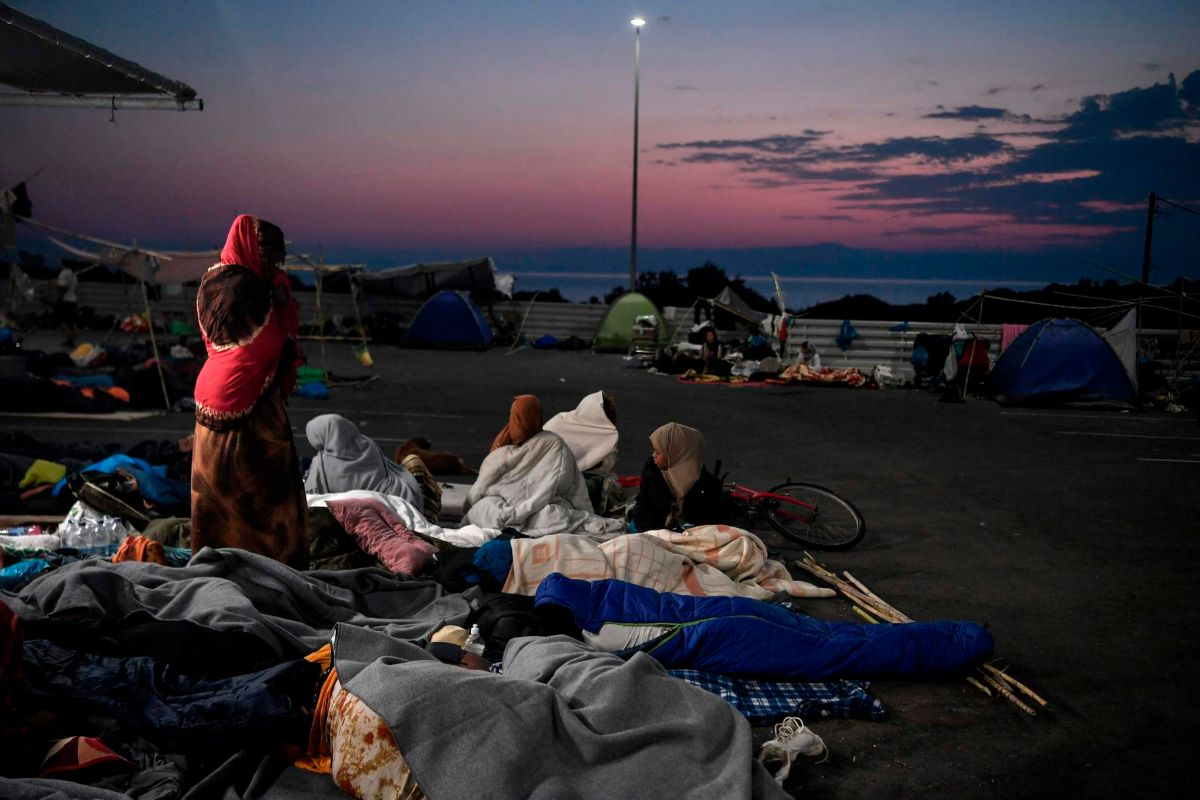 Refugiados y migrantes despiertan tras dormir al raso en Mitilene, tras el incendio del campo de Moria (Lesbos).