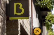 Logotipo de Bankia y CaixaBank en dos oficinas consecutivas de las entidades.