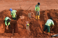 Trabajadores funerarios cavan tumbas en un cementerio de Yakarta.