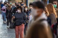 Varias personas pasean con mascarilla por las calles de Praga.