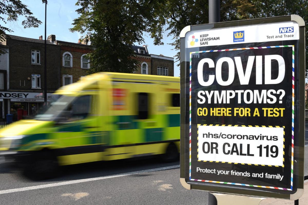 Una ambulancia pasa cerca de un cartel que invita a hacerse la prueba del Covid-19.