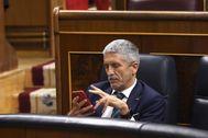 El ministro del Interior Grande-Marlaska consulta su teléfono móvil durante un pleno en el Congreso de los Diputados.