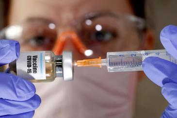 """Una mujer con un frasco etiquetado como ?Vacuna-covid"""" en una imagen de abril."""