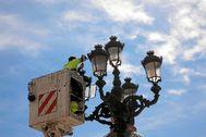 Un operario cambia la luminaria de una farola de Valencia.