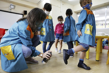 Una profesora desinfecta los zapatos de un alumno, en el colegio concertado Trilema El Pilar