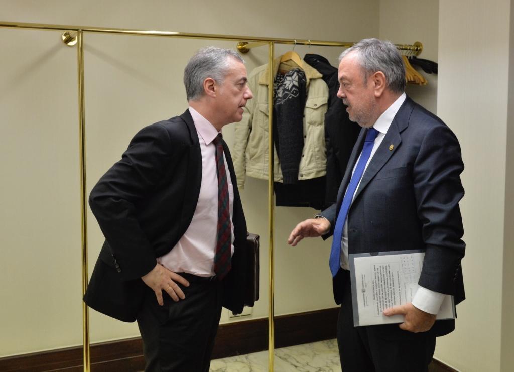 El lehendakari Urkullu conversa con el consejero de Economía Pedro Azpiazu en los pasillos del Parlamento Vasco.