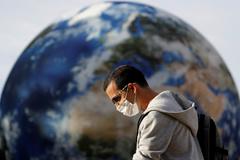 Un hombre con mascarilla por el coronavirus pasa ante un mural de la bola del mundo.