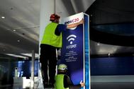 Un operario coloca un cartel informativo del MWC20.