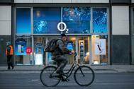 Un ciclista delante de una tienda de O2, marca de Telefónica, en Berlín.