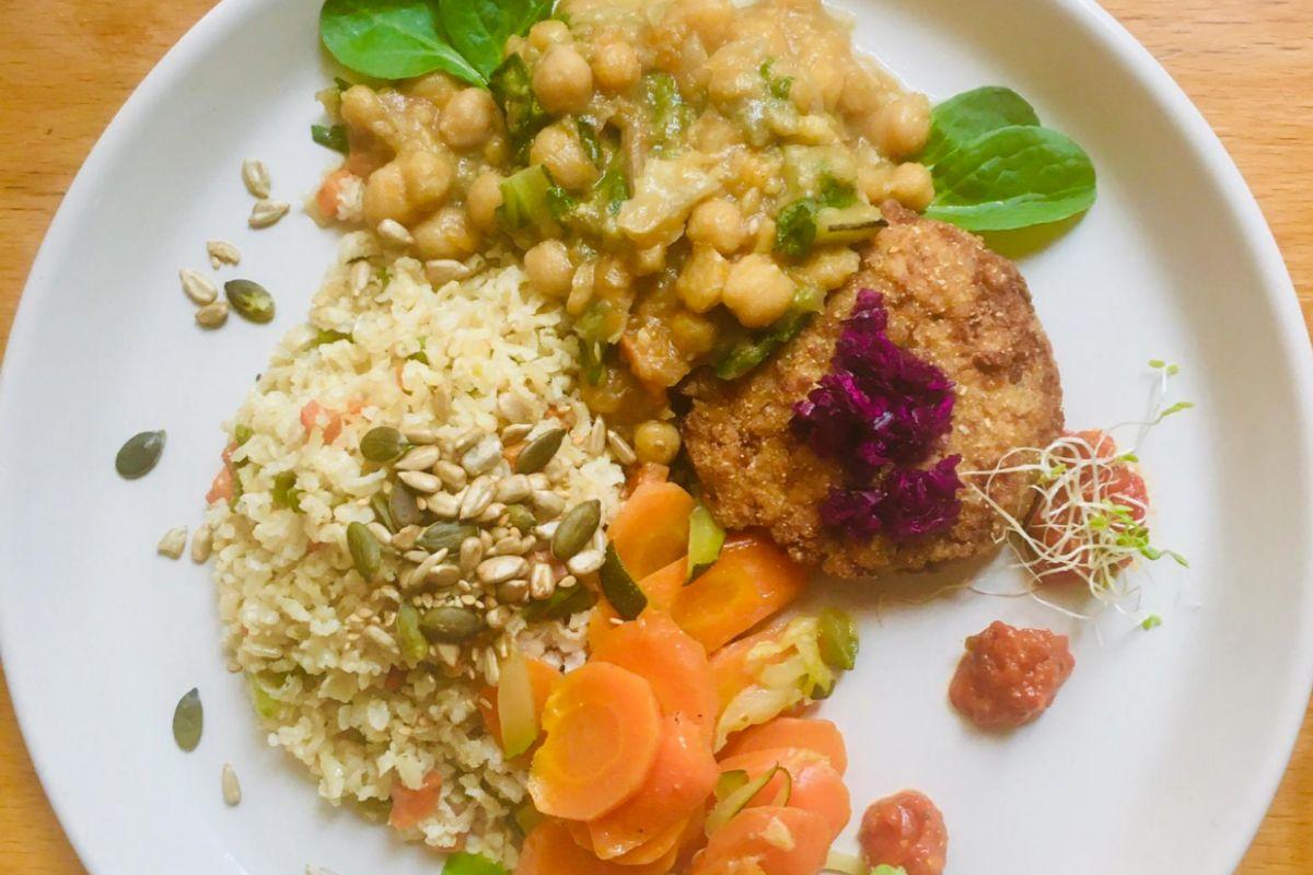 Plato del menú macrobiótico de La Biótika: estofado de garbanzos, arroz integral con semillas, tempura de coliflor y zanahorias al vapor.